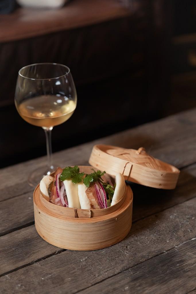 Momofuku style pork Bao bun with pickled veg, salted cucumber & sriracha aioli